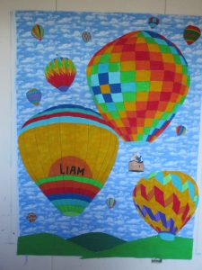 Child's quilt with hand-painted balloons and photos of the family in the balloon's basket