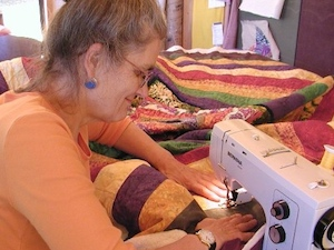 Kristin Miller stitching an over-size quilt.